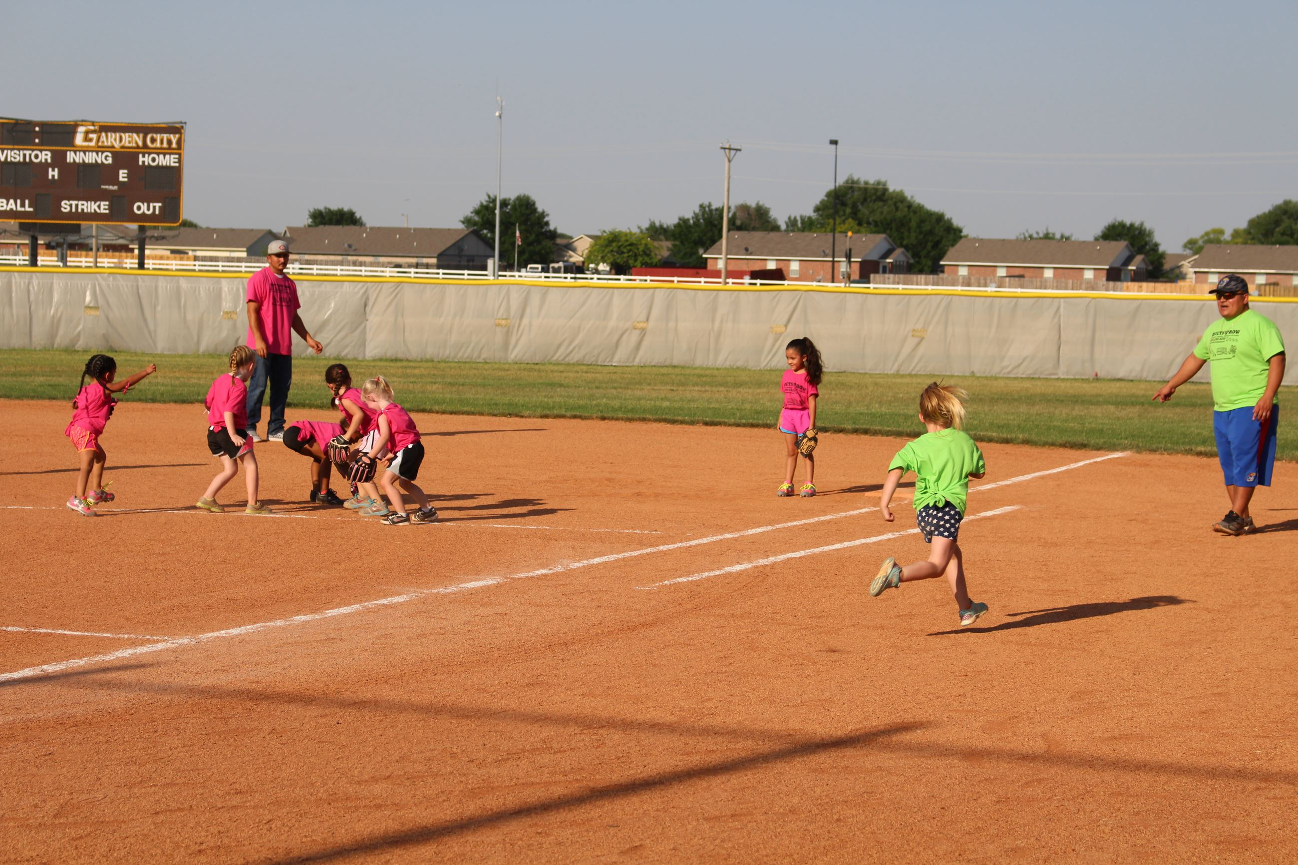 Girl running to first while the ball is being fielded by a group of players
